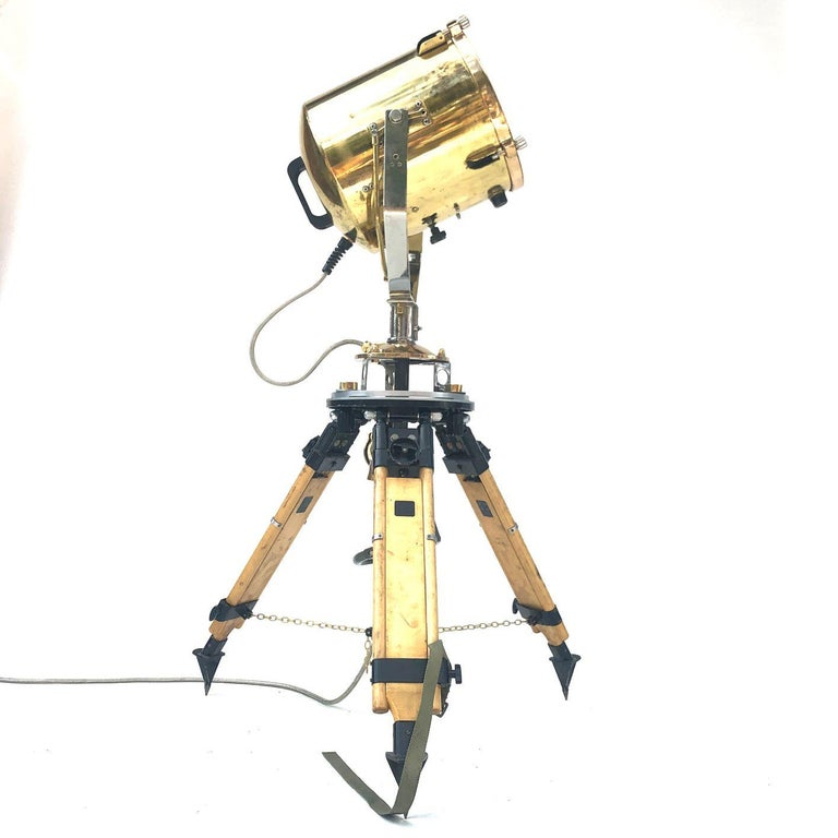 A reclaimed retro industrial British brass search light manufactured by Francis in 1980s coupled with a Russian military gyroscope tripod.  There is a circular handle inside the tripod which is used to mechanically pan and tilt the lamp.
