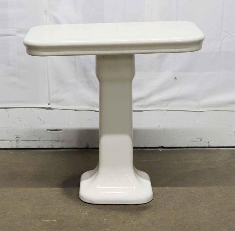 1980s white ceramic rectangular top bathroom console table done in an Art Deco styling from France. This can be seen at our 400 Gilligan St location in Scranton, PA.