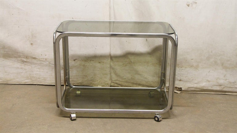 1980s bar cart with a chrome frame and dark glass shelves from France done in a Mid-Century Modern style. This can be seen at our 333 West 52ndSt location in the Theater District West of Manhattan.