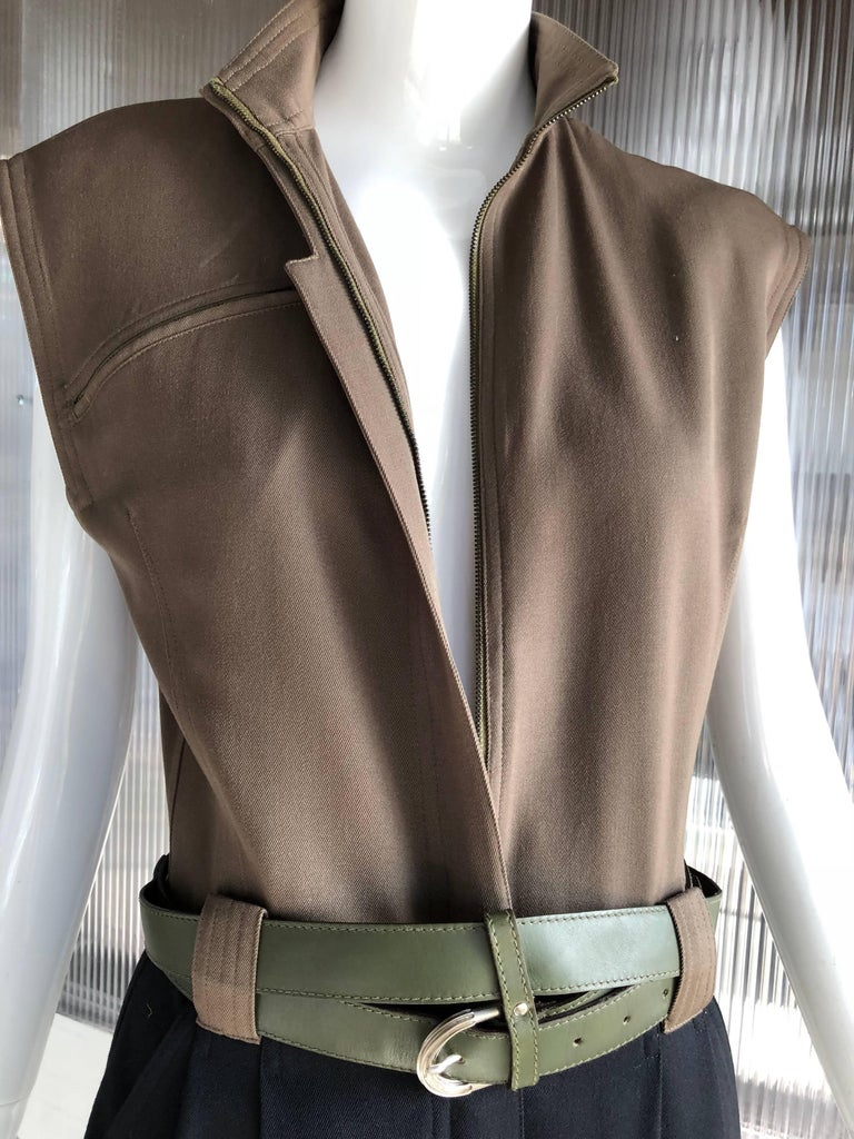 A wonderful 1980s Gianni Versace 2-tone gabardine jumpsuit in black and army green gabardine. Featured with a Gianni Versace olive green double wrap belt. Pleated front, men's-style tailoring. Slightly padded shoulders. Nehru collar. Front zipper.
