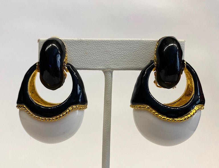 A stylish and chic pair of late 1980s door knocker style dangle earrings. Each clip earring is gold plated with black enamel on top and a large oval white lucite cabochon set into the bottom. The interior of the earrings and rope border around the