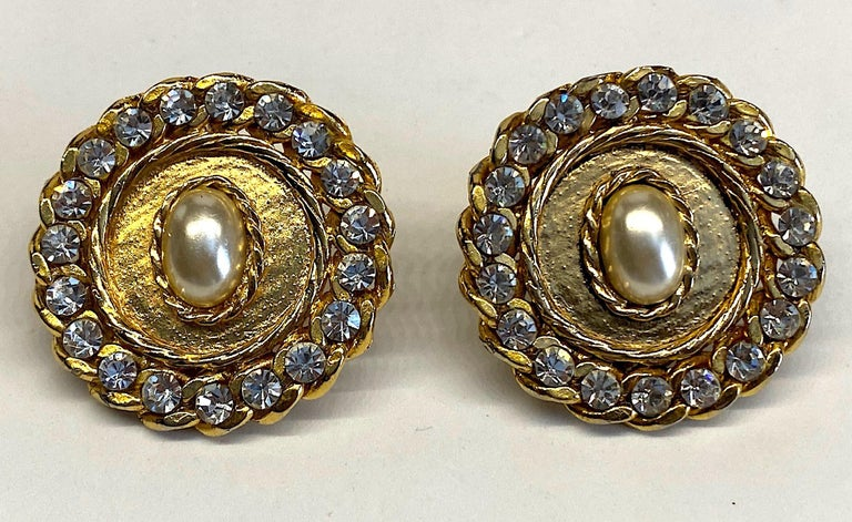 A large pair of 1980s button medallion earrings. Each earring is 1.75 inches in diameter and has an oval faux pearl cabochon in the center. The pearl is surrounded by a rope twist braid and matching curb link chain set with rhinestones. They are