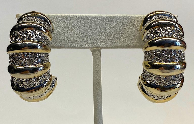 An eye catching pair of large 1980s half hoop earrings in gold and rhodium plate and accented with rhinestones. The Each earring measures .63 of an inch wide, 1.5 inches high and 1 inch deep not including the clip back. Very good condition.