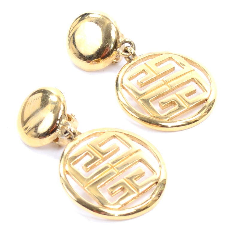 Beautiful gold tone Givenchy logo clip on dangle drop earrings. These great designer earrings  have a solid circular piece that clips to the ear, with a drop circle containing the cutout Givenchy logo. They are marked