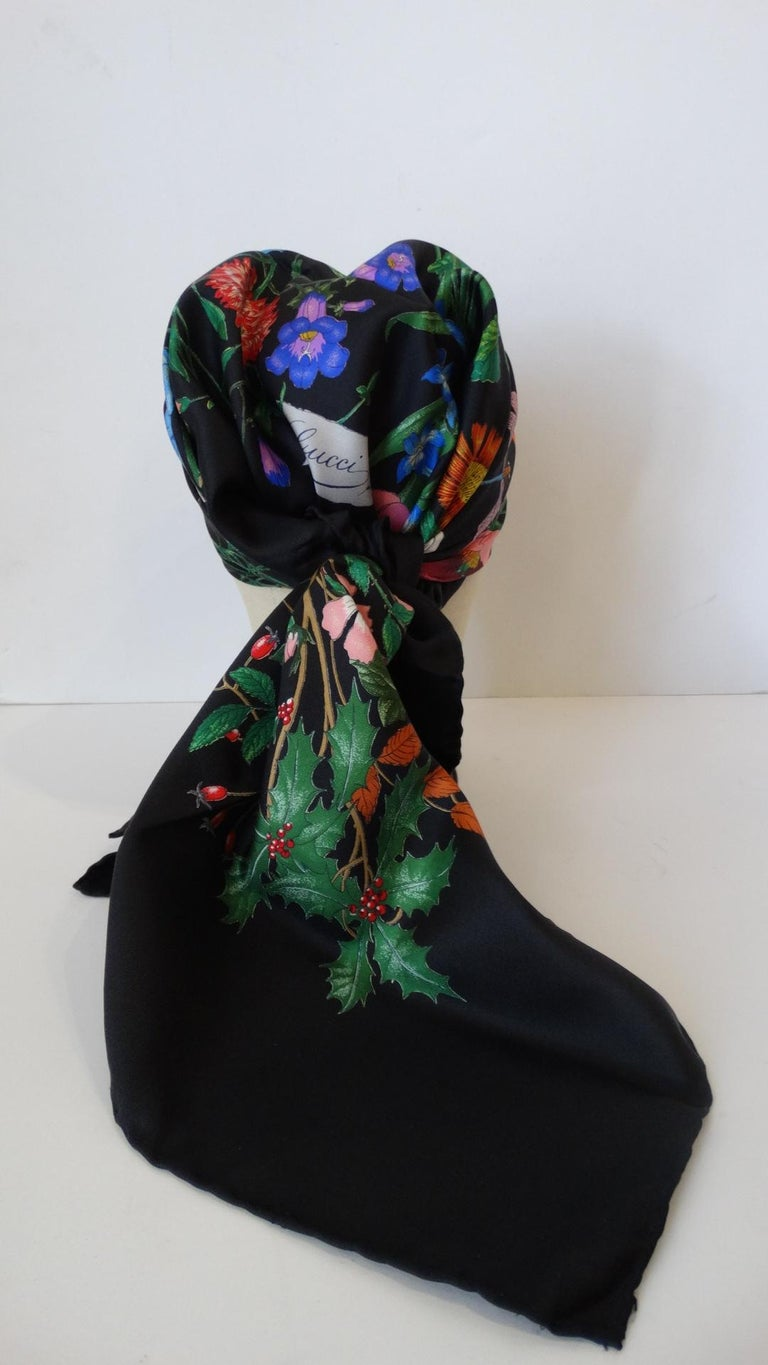 """Who doesn't love a little vintage Gucci Flora? Incredible black silk scarf printed with Gucci's signature multicolored """"Flora"""" floral print! """"Gucci"""" printed in cursive in the bottom corner of the flowers. The size of this scarf allows for a number"""