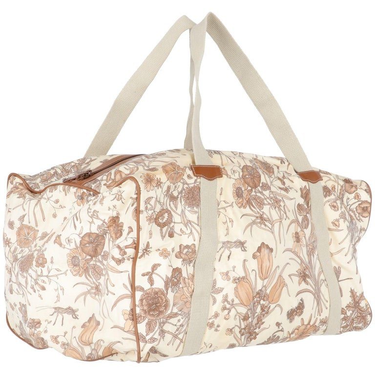 The Gucci beige canvas duffle bag features a brown and beige flora and fauna print, with zip fastening, outer side zipped pocket, ivory lining and gold-tone branded inner tag. The item shows stains and signs of wear at lining and on the canvas, as