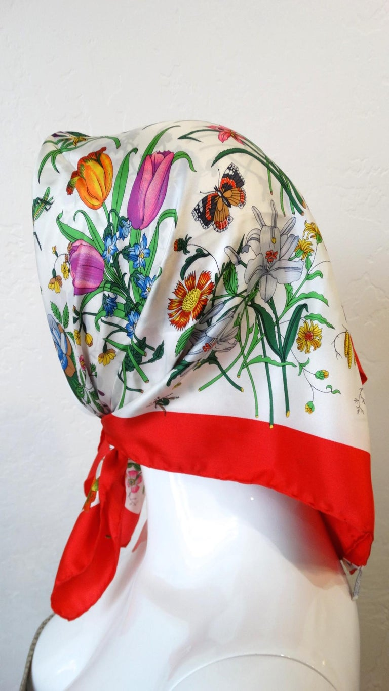 We Will Never Be Over Gucci Flora! Circa 1980s, this Gucci scarf features the iconic flora print which includes a variety of flowers, crickets, butterflies, and beetles. Includes a vibrant cherry red trim. Is signed Gucci in the signature cursive