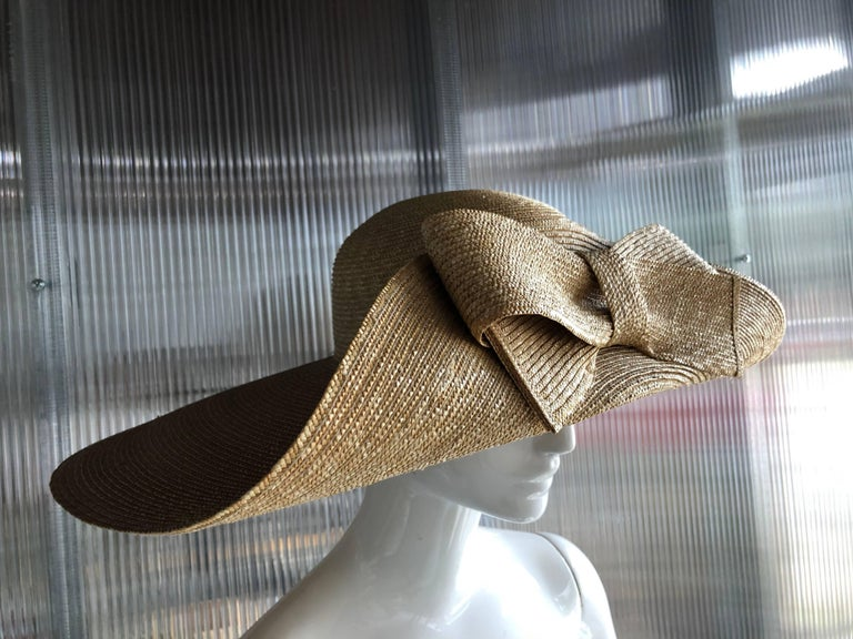 A striking 1980s Helene Berman wide brimmed natural straw hat, with the front brim folded and embellished with a large straw bow!  Perfect for a wedding or the races!