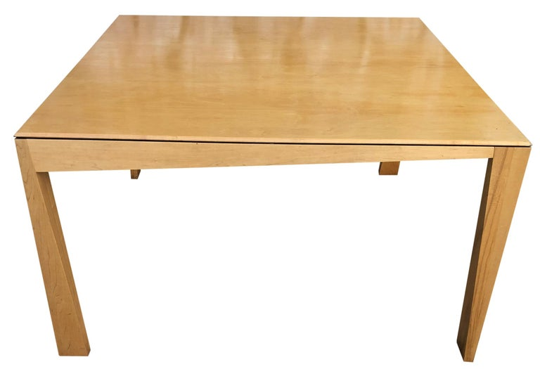 Beautiful 1980s Hennie de Jong square asymmetrical leg maple square dining table blonde maple finish, Sculptural design. Very delicate designed dining table with asymmetrical legs. Solid maple. You are buying (1) dining table. Fits up to 8 chairs.
