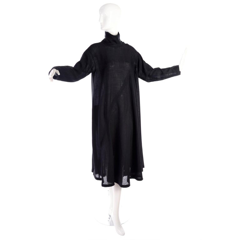 This is a truly iconic vintage 1980's Issey Miyake tent mock turtleneck dress in his signature style in a lightweight black wool crepe.  The dress has long sleeves and buttons at the neck.  Labeled a size small, the dress has a versatile fit because