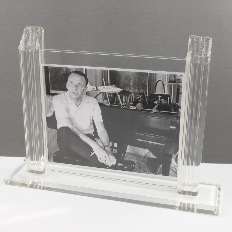Beautiful modernist Lucite picture photo frame designed by Oggi design, Italy. Large and thick crystal clear Lucite base with beveling topped with large carved pole holders finished with an unusual rough carving on top. Two sheets of acrylic to hold