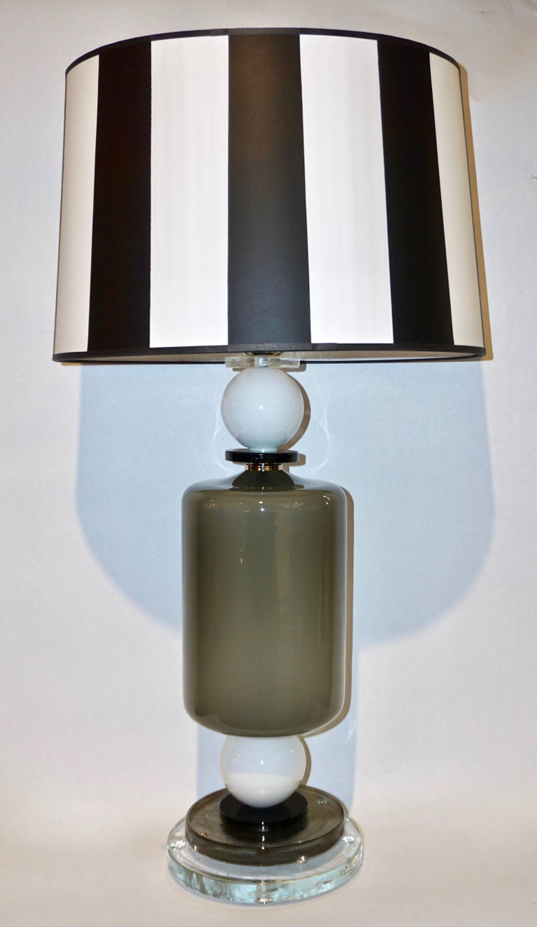 A fine Italian Design pair of modern table lamps of geometric shapes. The central cylindrical body in radiant grey blown Murano glass highlighted with two white spheres and black round accents is supported by a high quality stepped round base,