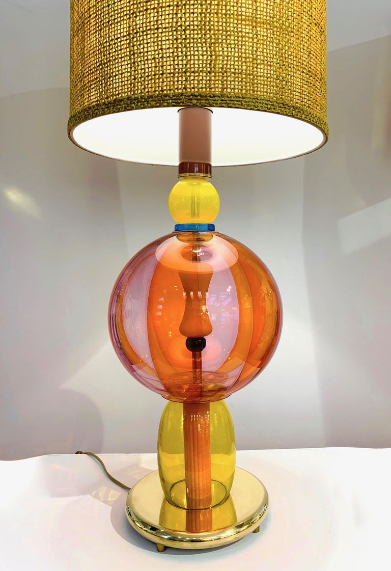 1980s one-of-a-kind Memphis style Italian table lamp, entirely handcrafted, consisting of a succession of different glass elements in blown Murano Art glass in various shapes with a typical Pop Art palette in orange, yellow, purple plum with a