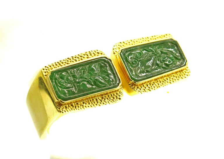 Chic and stylish 18 karat gold bangle bracelet featuring 2 rectangular plaques of jade. The beautiful forest green translucent shows detailed engraving of a floral motive, set in a bezel and surrounded by detailed granular gold-work. The rest of the