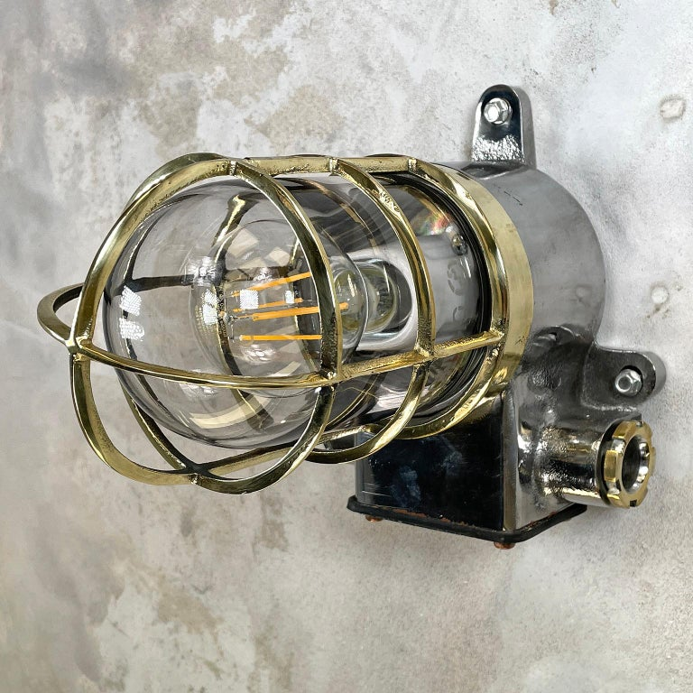A vintage Industrial 1980s Japanese cast iron wall sconce with a brass cage and glass shade manufactured by Kokosha.  Reclaimed and professionally restored by hand in UK ready for contemporary interiors.  Perfect wall lighting to add some rustic