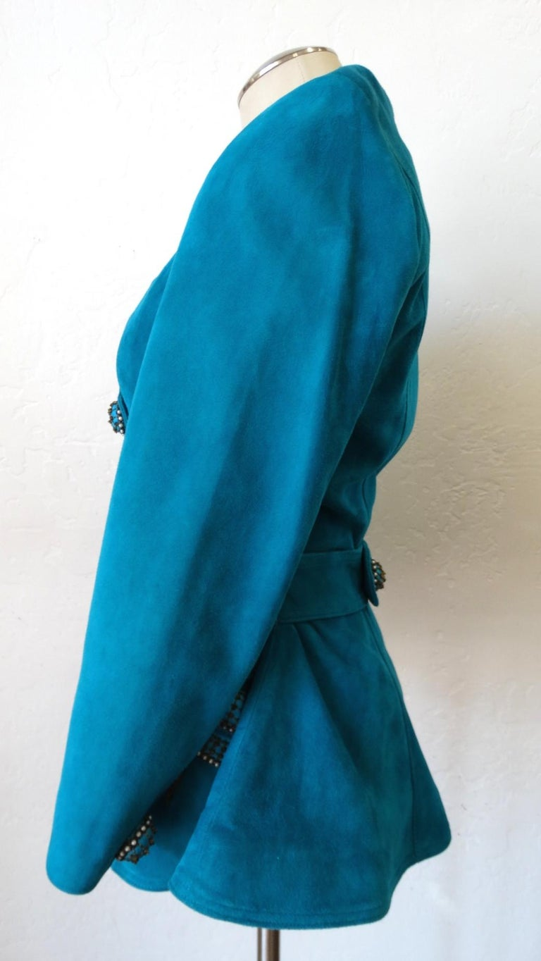 This Jacket Is Just Waiting To Be Worn! Circa 1980s, this Jean Claude teal suede leather double breasted jacket features a flattering sweetheart neckline and is decorated with embellished buttons and bows. The snap closure button and bow accents