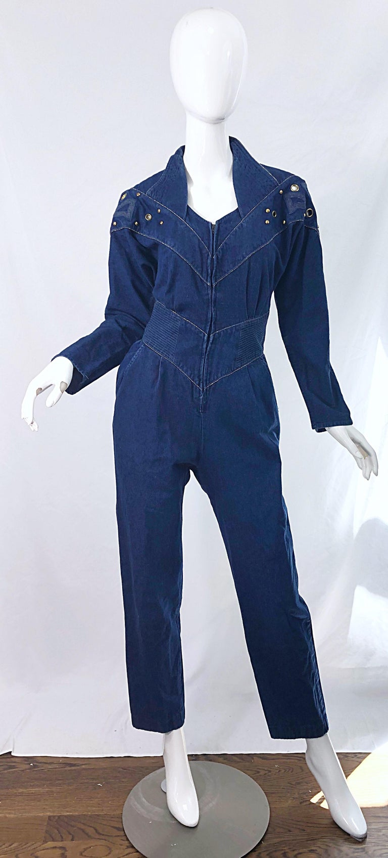 Avant Garde JILLIAN ARTHUR blue jean denim one piece jumpsuit ! Features gold studs and grommets along the front and back dolman sleeve bodice. Hidden zipper up the front. Pockets at each side of the hip.  Made in USA Approximately Size Medium /