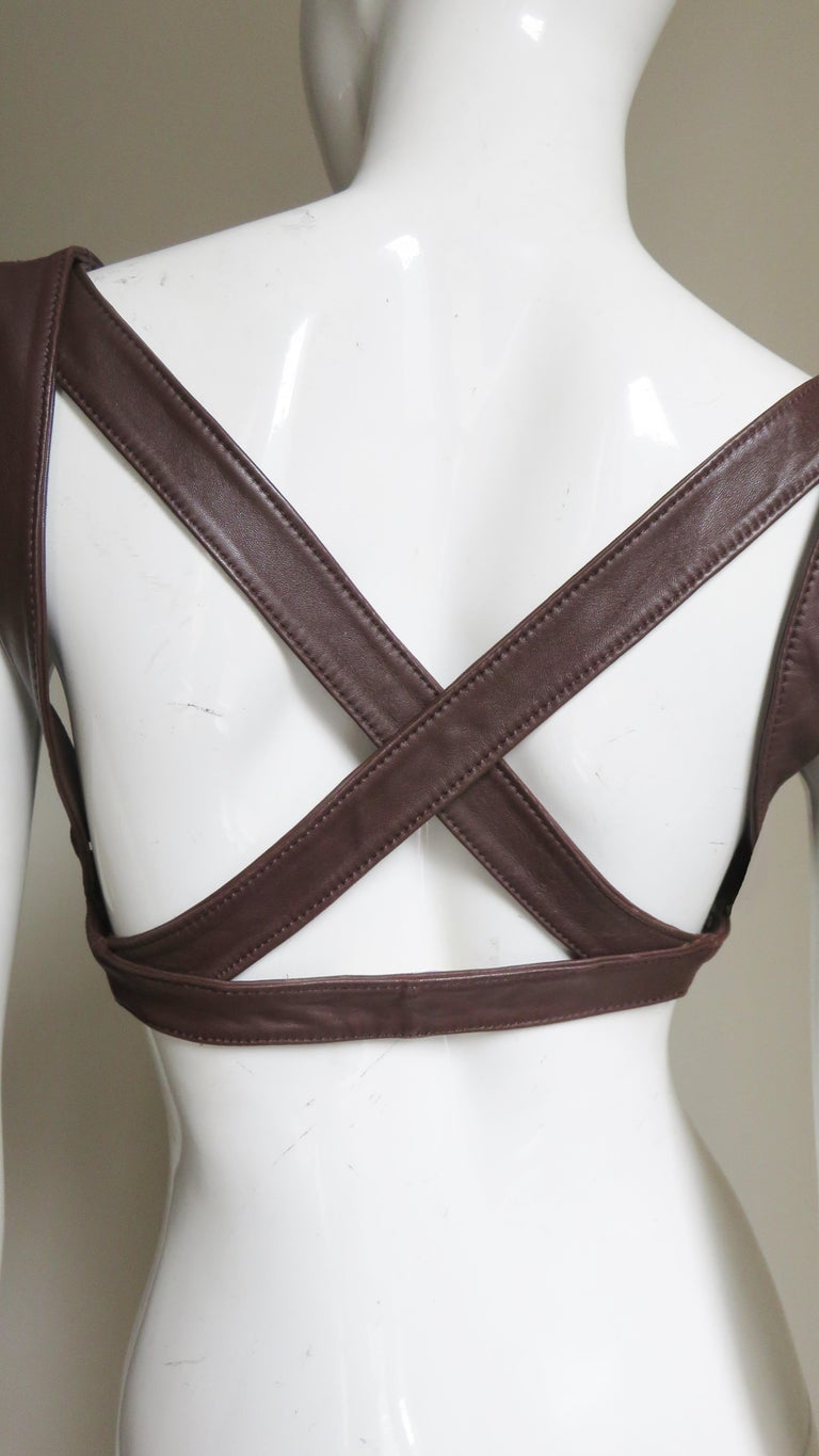 A fabulous brown leather harness by Krizia.  It has straps at the shoulder, crossing at the upper back and around the mid back closing in the front under the bust with a gold metal clasp.  Fits Extra Small, Small, Medium.  Under Bust  30