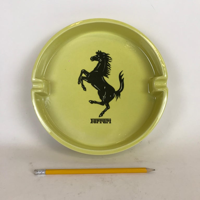 Ferrari advertising ashtray in yellow ceramic made in Italy by Bitossi in the 1980s. This large circular ashtray has a black Ferrari horse symbol in the centre and one Ferrari logo outside on the border. It's also marked Bitossi on bottom. 