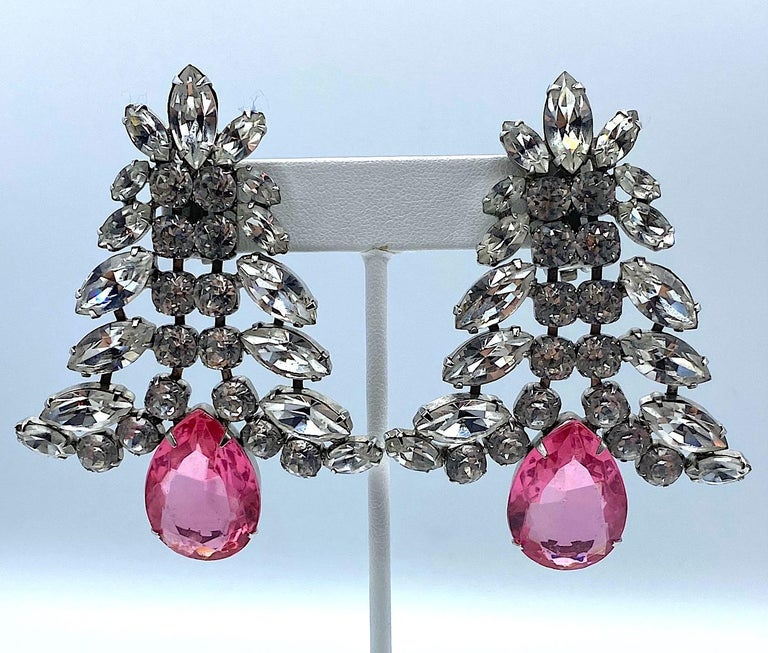 A fabulous pair of large rhodium plated and rhinestone set earrings with pink crystal stone. The earrings are set with round rhinestones along the center with various size marquise shape rhinestones along the top sides forming a bell shape. The