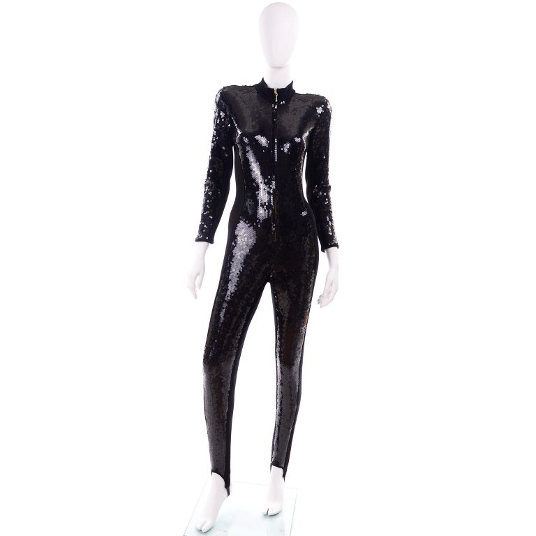 This is an absolutely stunning vintage zip front black sequin jumpsuit from Lillie Rubin. This 1980's  stretch jumpsuit contours to the shape of the body and the shoulder pads and fitted waist make it an extremely flattering fit.  We love the