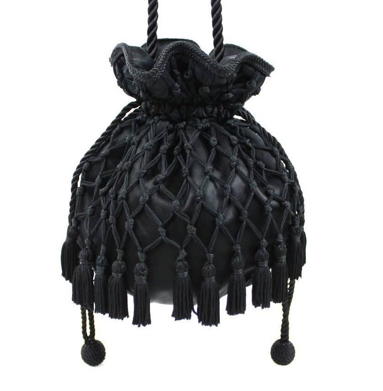 The most elegant little tassel bag from 1980s Lord & Taylor! Black satin drawstring pouch wrapped in braided netting, with tassel trim all along the bottom. Bag pulls closed with two drawstrings, each with a cord ball at the end. Long, twisted cord