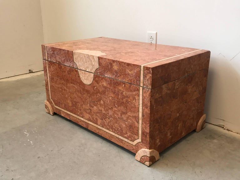 Offered is an exquisite, Robert Marcius for Casa Bique trunk, circa 1980s. Covered in tessellated marble stone of contrasting coral shades, with squared feet that have a contrasting rounded inner edge, adding sculptural detail to the piece. Brass