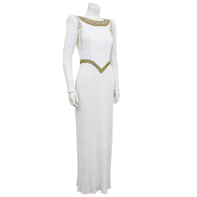 1980s fabulous white micro pleated Mary McFadden gown. Long sleeves with fitted bodice and straight skirt. Beautiful metallic gold macramé and pearl neckline, gold wrapped rope detail at shoulders and gold v shaped detail at waist. Would be a