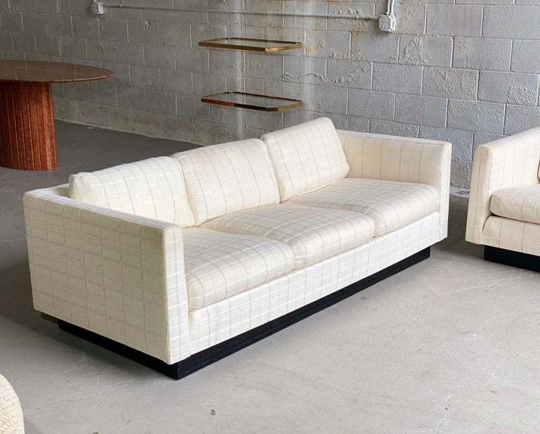 We are very pleased to offer a pair of super chic, tuxedo sofas designed by Milo Baughman for Thayer Coggin, circa the 1980s. This set showcases a wraparound frame upholstered in a beautiful neutral linen fabric supported by a black plinth base.