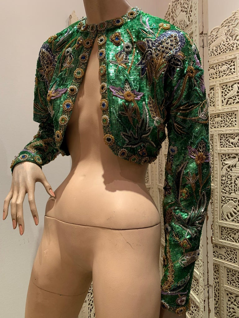 A wonderful 1980s Oscar de la Renta evening bolero jacket with rounded hem and dolman sleeves, entirely covered in an exquisitely beaded and sequined thistle pattern of emerald green and purple. Rows of jeweled medallions adorn the edging and cuffs.