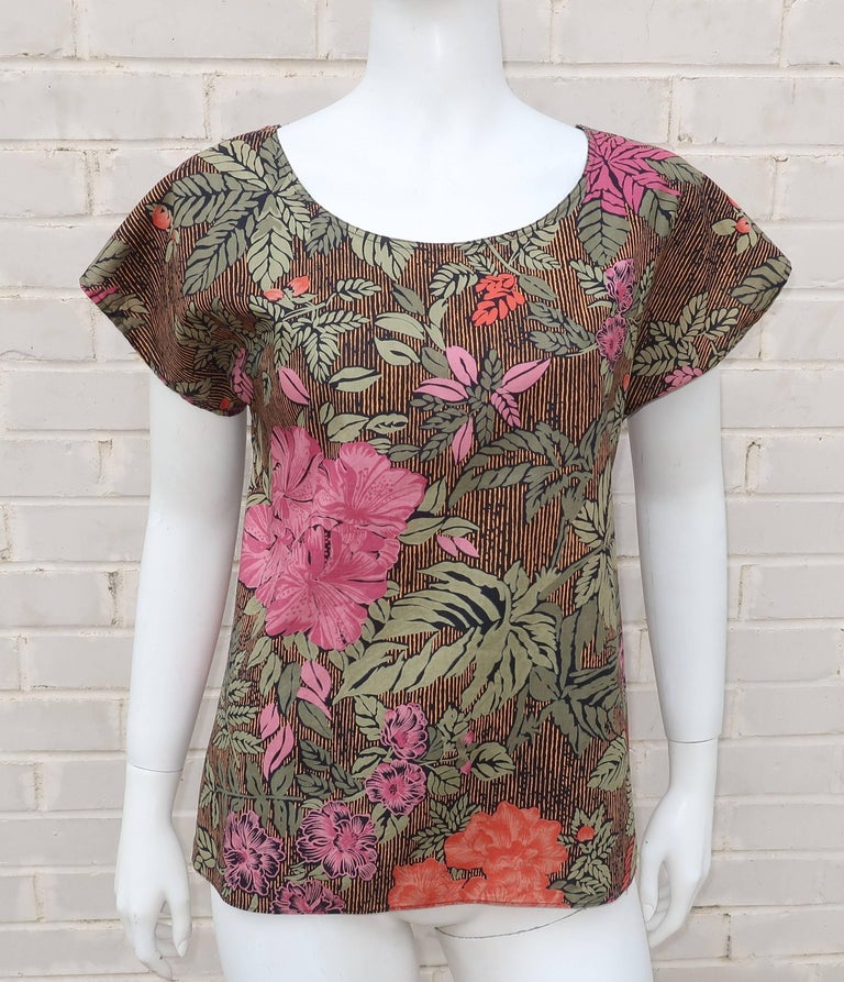 This Oscar de la Renta Sport top is a dark tropical floral pattern incorporating shades of pink, coral red, greens, black and a golden yellow.  The pullover style is easy to wear with short sleeves and a loose silhouette.   Perfect to pair with a