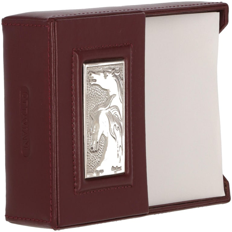 The elegant and classy Ottaviani bordeaux leather desk paper holder is embellished by a front silver detail with horses-embossed and a branded detail, on the side. The original dustbag, the box and authenticity card are included.  Year: 1980 Made in