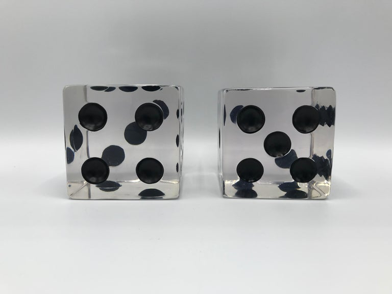 Listed is a fabulous and unique, pair of 1980s oversized Lucite game dice sculptures. The pair would be perfect on any tabletop or shelf. Large enough to be used as bookends. Heavy, weighing 2lbs each.