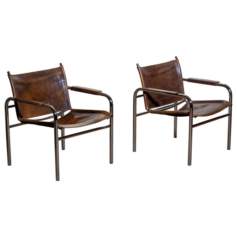 Beautiful pair of armchairs, model Klinte, designed by Tord Bjorklund, Sweden. The chairs having a tubular chromed steel frame with brown-taupe leather back / seating and armrest with a beautiful patina.