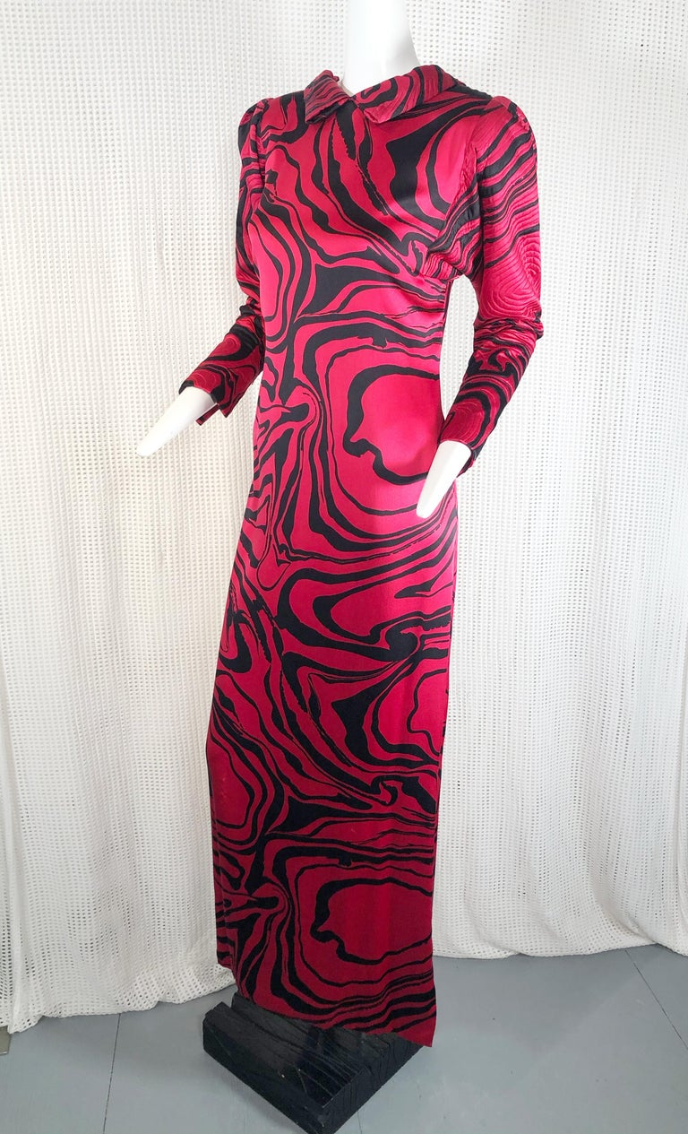 A wonderful design by Pauline Trigere in a marbleized silk charmeuse print with a low back and criss cross strap design. Features include quilted puff shoulders and tapered sleeves.  High quilted collar that folds low to the back.   Gown is