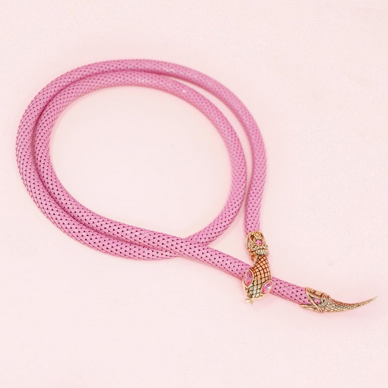 This gorgeous belt, which can also be worn as a necklace, is constructed of an innovative pink powder coated mesh material with gold tone snake head and tail embellishments.  The snake head possesses matching pink rhinestones with intricate