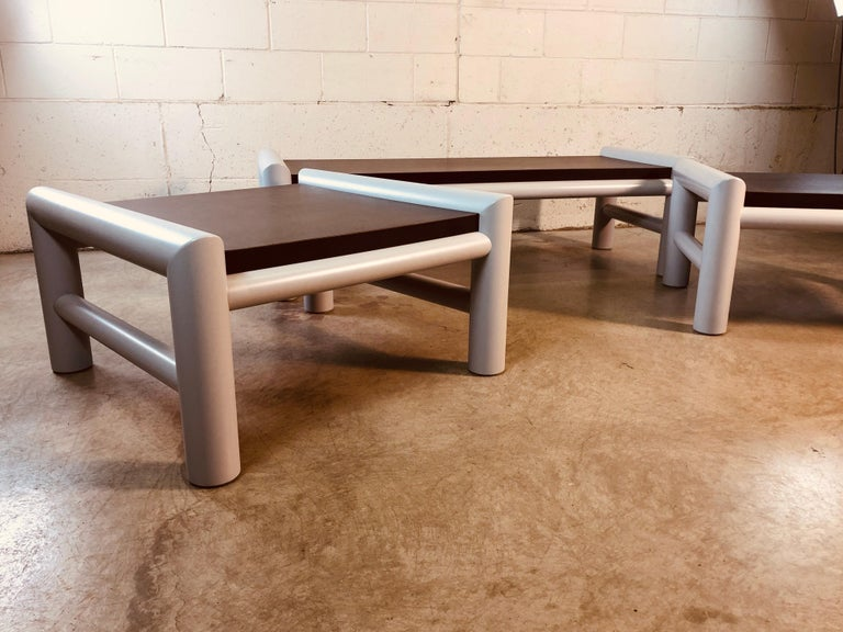 1980s set of 3 indoor or outdoor plastic table set. The set includes the coffee table, large square side table and smaller rectangular side table. The frames are plastic and the tops are MDF. The tables have all been sanded, painted and restored. No