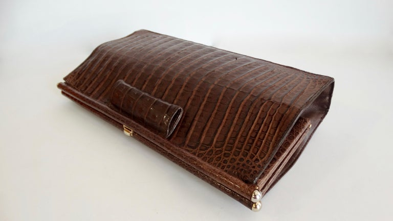 Elevate your purse collection with this Donna Karan clutch! Circa 1980s, this rare clutch is made of genuine caiman crocodile. Features a simple and timeless design and includes a push tap closure. Interior is fully lined in black suede. The perfect