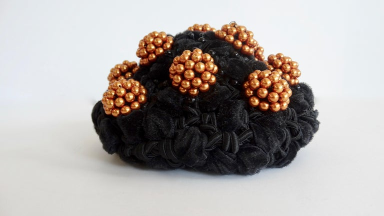 Elevate your headwear with this adorable bun cover! Circa 1980s, this Isabel Canovas bun cover is made of intertwined black fabrics and is embellished with copper colored bead clusters. Small black beads are scattered throughout for a subtle accent.