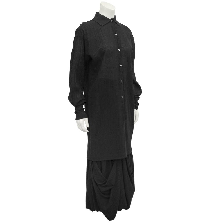 1980s Romeo Gigli black natural cotton ensemble. Long tunic blouse with a knit collar and small grey mother of pearl buttons. Loose fit through body, but tapers towards hem. High waisted maxi skirt with ruching and large pick ups creating beautiful