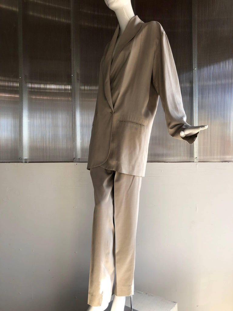 A 1980s Romeo Gigli over-sized fit fluid and lanky 2-piece menswear inspired suit in sandstone washed silk.  Double breasted jacket with full-cut back and loose flowing pleated, high-waisted pants.