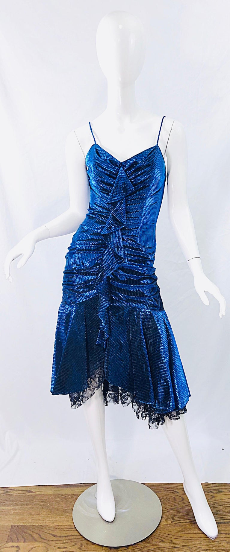 Sexy 1980s SAMIR metallic electric blue lurex and black lace handkerchief hem slinky spaghetti strap dress ! Features a flattering ruched body, with a ruffle down the center. Innner boning keeps everything in place. Hidden zipper up the back. Looks