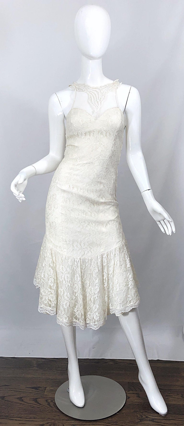 Fabulous 1980s SAMIR ivory / white lace embroidered handkerchief hem cocktail dress! Features a sweetheart neckline with a mesh embroidered overlay above the bust. Satin bow at center back, just above the rear. Hidden zipper up the back with