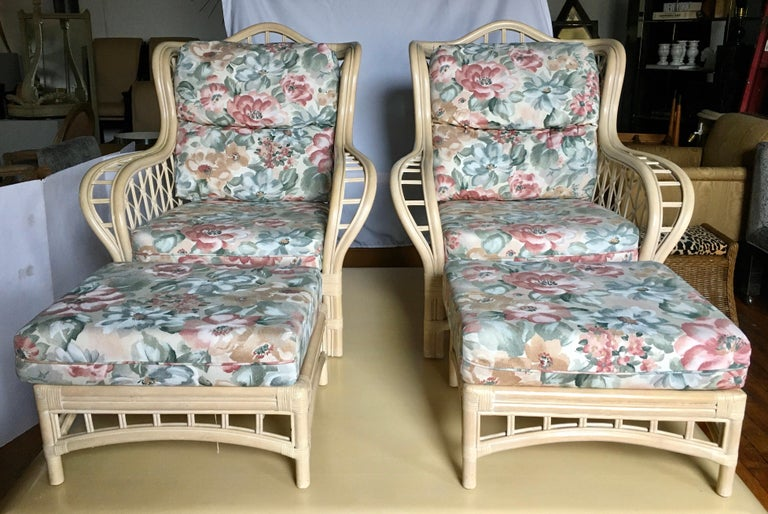 Pair of rattan faux bamboo wing chairs and ottomans by Lane. These large sculptural curved lounge chairs have original removable seat and back floral print cushions which can easily be reupholstered. Pair of ottomans also have original removable