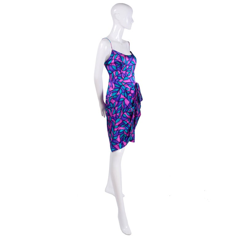 This colorful vintage silk dress was made by AJ Bari in the 1980's. The 80's were definitely back on the runways in designer collections for 2018/19 and we think this dress fits perfectly into that trend with its hemline and side drape. The purple,