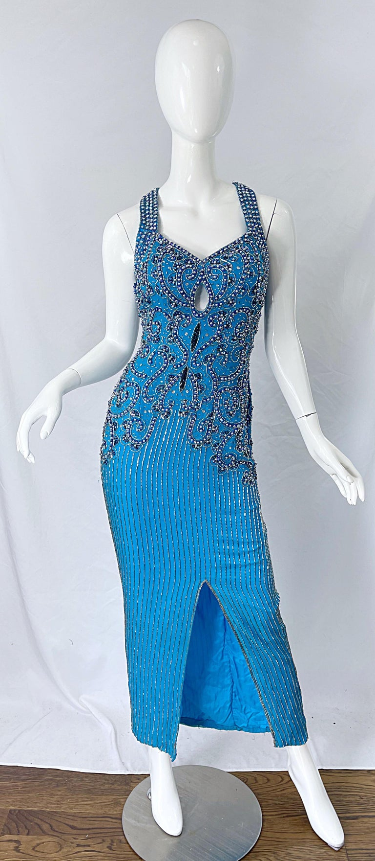 Beautiful 1980s TED LAPIDUS turquoise blue silk beaded evening halter gown ! Features thousands of hand-sewn beads in silver and blue, sequins in blue and pearls throughout the entire dress. Peek-a-boo detail at center bust. Hidden zipper up the