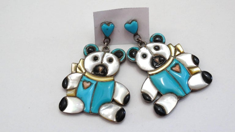 Rock a novelty earring with our adorable 1980s Zuni teddy bear earrings! Made of 100% silver. Heart shaped posts with Zuni turquoise inlayed, with pierced backings. Dangly teddy bear pendants with inlays of iridescent pearl, turquoise and black onyx