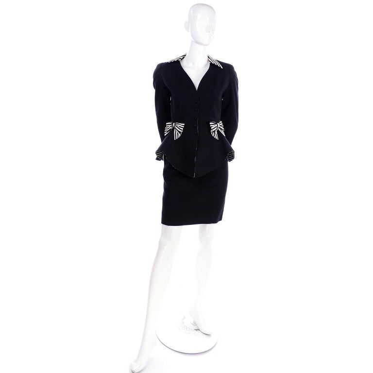 This is a vintage 1980's black cotton pique skirt suit designed by Thierry Mugler.  The peplum style blazer has black and white striped upturned cuffs, collar and bows.  We love that the peplum itself is lined with the same black and white stripe