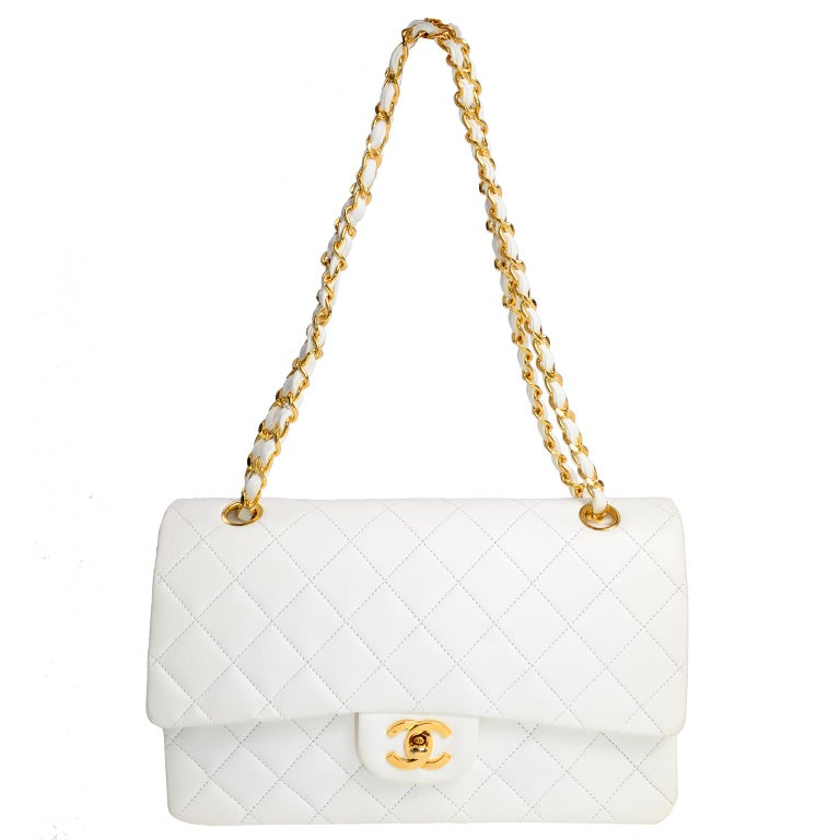 This is an unused vintage but new Chanel white quilted medium flap bag with its original tissue inside.  Beautiful gold hardware and leather and gold chain strap. The bag comes from a single owner who never used it and kept it with the original