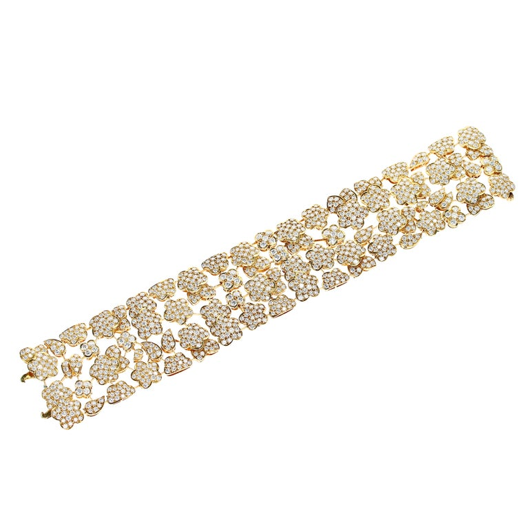 A remarkable, impressive, and highly fluid 1980s Van Cleef & Arpels yellow gold bracelet with star, cumulus cloud, paisley, and Alhambra motifs masterfully linked and set with over nine-hundred round brilliant-cut diamonds, approximately F/G-color,